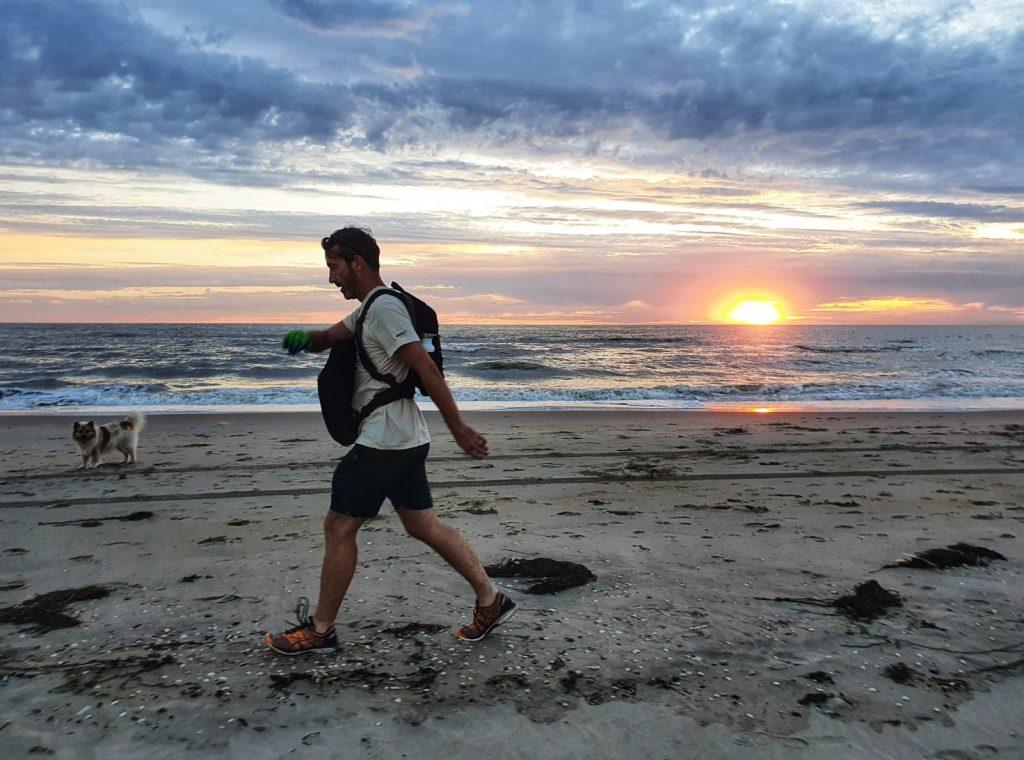 Daan op het strand bij zonsondergang zwerfafval aan het opruimen