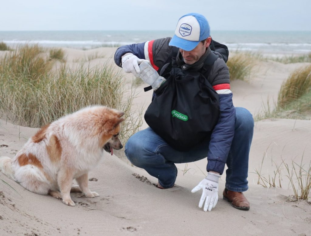 Daan die zwerfafval aan het opruimen is op het strand