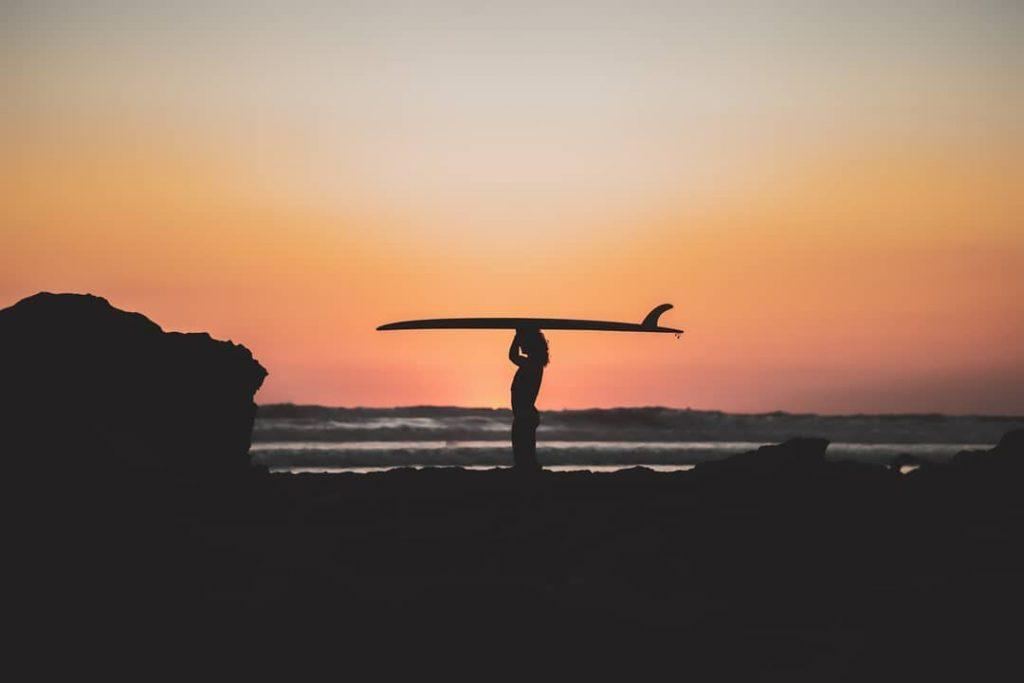 Anne met haar surfboard bij zonsondergang